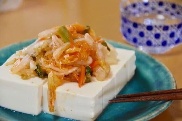豆腐の上にキムチが乗っている 日本酒も一緒に