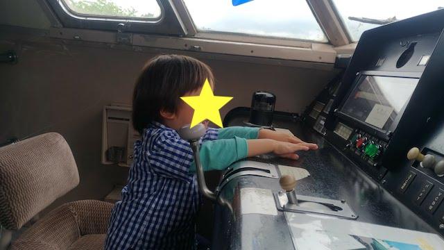 新幹線の操縦席に座る男の子