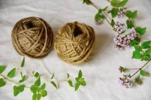 オレガノとオレガノで染めた毛糸が布の上に置いてある