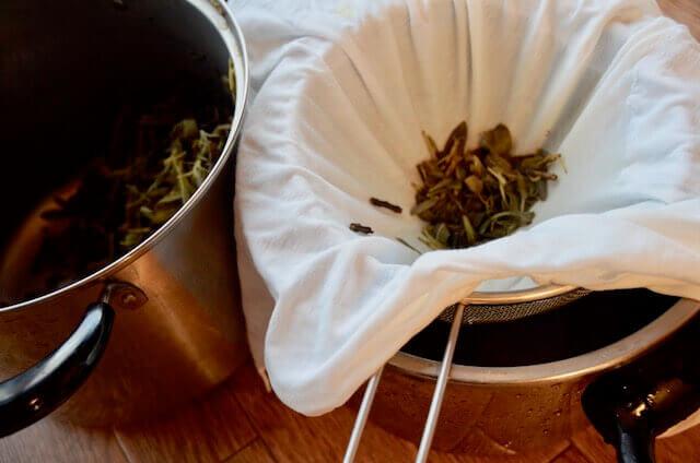 ザルと鍋を使ってセージの染色液を濾す