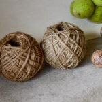 胡桃染の毛糸と生のくるみが胡桃染の布の上においてある