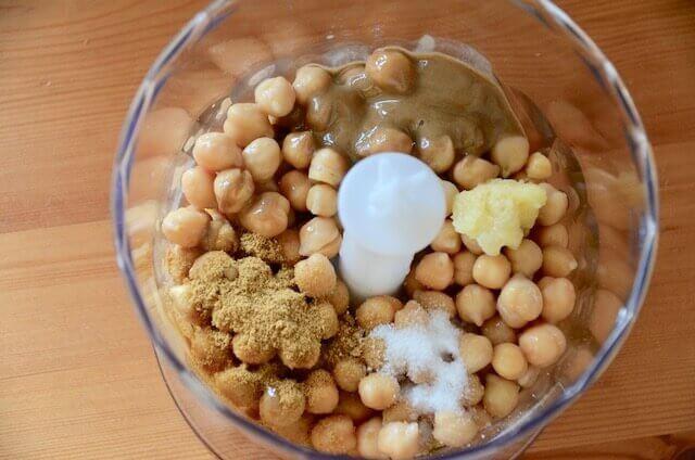 フードプロセッサーにひよこ豆、クミン、にんにく、塩、オリーブオイルが入っている