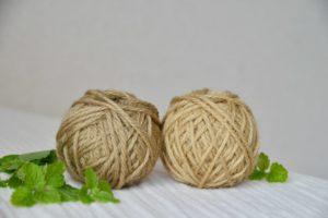 レモンバーベナ染めの毛糸が2玉レモンバーベナの葉と一緒においてある