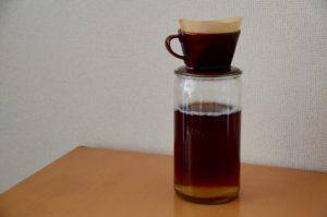 コンブチャ作成過程 1.5リットル入りの耐熱容器瓶の上にコーヒードリッパーが置かれ、紅茶を濾している
